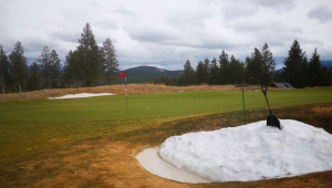 Golfing in cold weather, there is snow in the greenside bunker